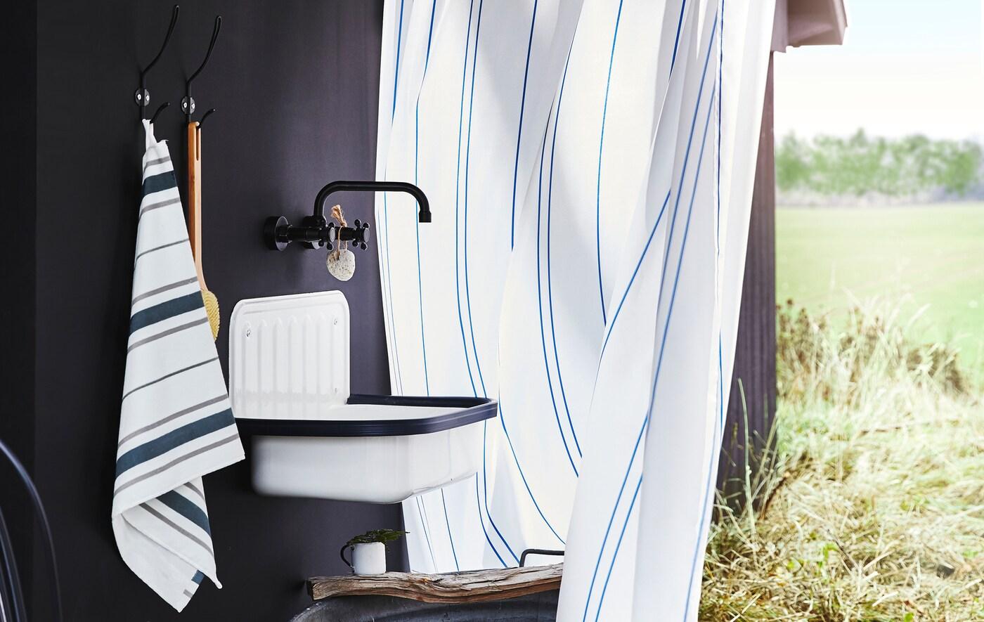 Una toalla, ganchos, un lavabo y un grifo en una pared negra, con un campo detrás de una cortina de ducha a rayas.