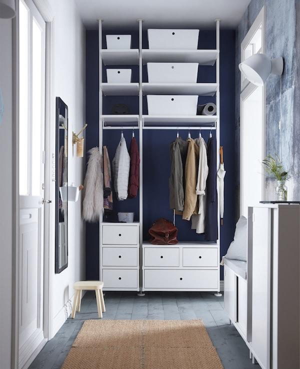 Una unidad de almacenaje blanco con un raíl para ropa, estantes y cajones, que va del suelo al techo en este estrecho recibidor.