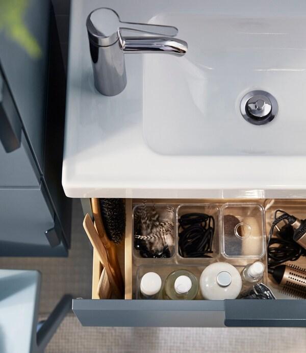 Una vista de pájaro de un fregadero de baño blanco y un cajón de armario azul abierto y con organizadores de plástico transparentes.