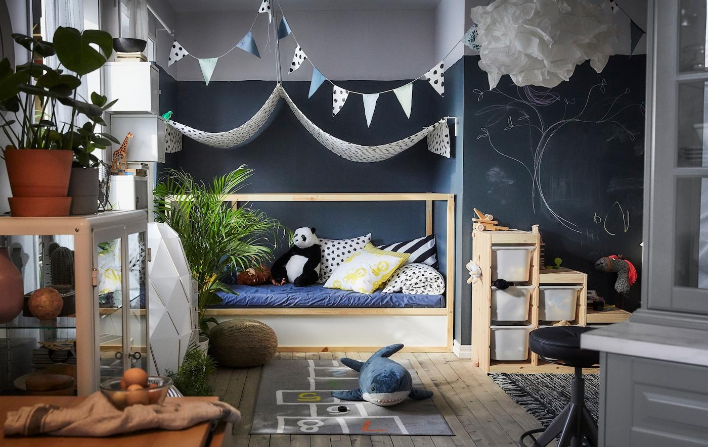 Una zona de juegos con un dosel de tela sobre la cama, peluches, una alfombra estampada y cajas de almacenaje.