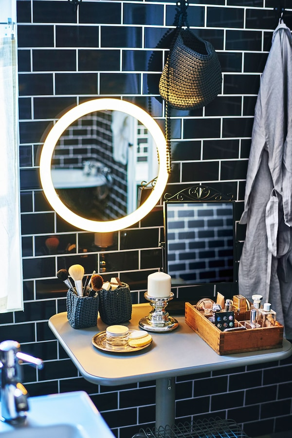 Una zona de maquillaje en el baño bajo un espejo iluminado con un baño de azulejos negros.