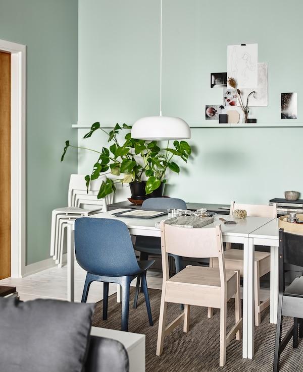 Una zona de menjador a una sala d'estar oberta amb taules MELLTORP blanques envoltades de cadires d'estils diferents.