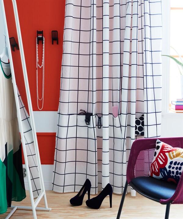 Una zona de tocador amb un mirall gran i una cortina blanca i blava IKEA ROSALILL amb butxaques cosides per als accessoris.