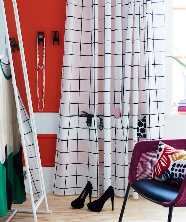 Una zona de tocador con un gran espejo y una cortina blanca y azul IKEA ROSALILL con bolsillos cosidos para accesorios.