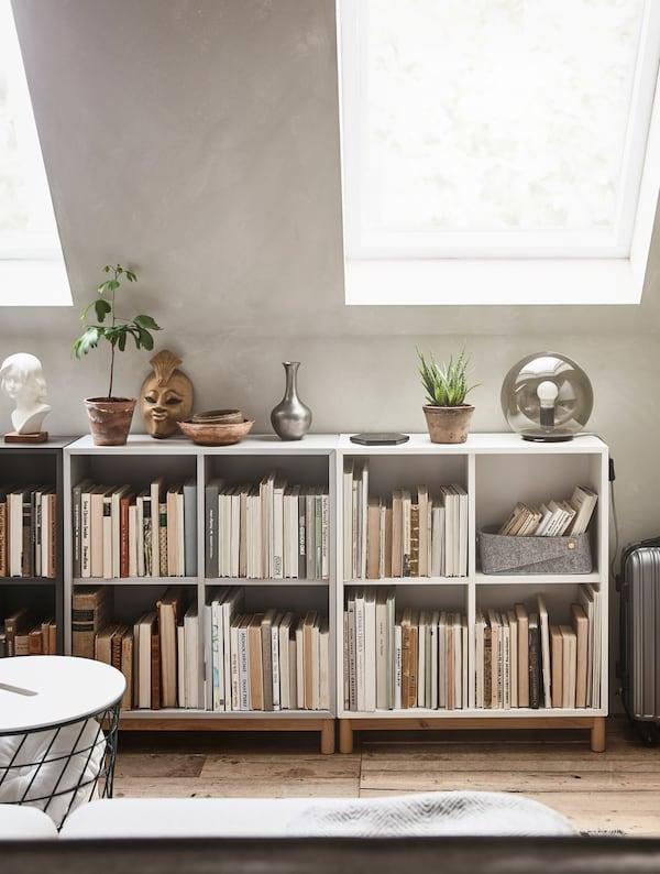 Unas estanterías bajas con libros y artículos decorativos y plantas encima.