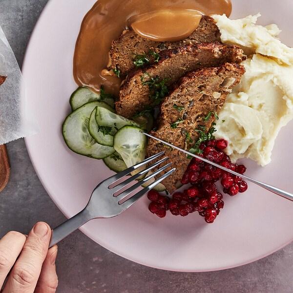 Unas manos con cuchillo y tenedor a punto de cortar el pastel de carne de proteína vegetal en un plato con pepinos en rodajas, arándanos rojos, salsa cremosa y puré de patatas.