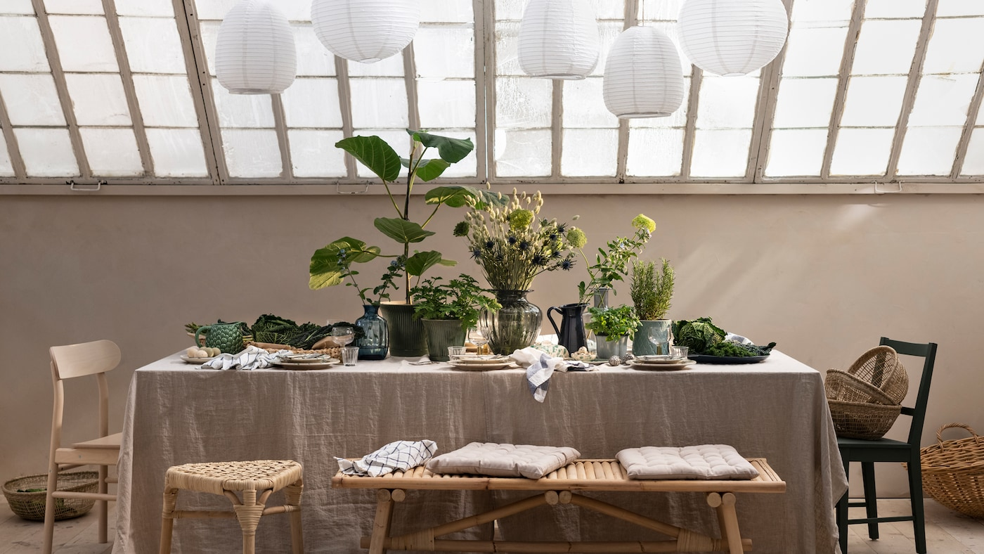 Under a glass roof is a table with a linen tablecloth, plates, and plenty of plants and branches in plant pots and vases.