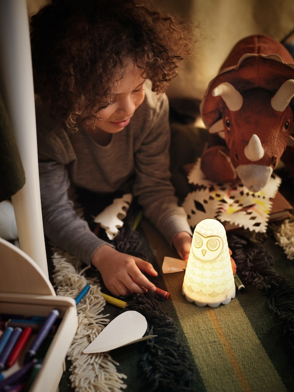 Under a table, a boy plays with a SOLBO night light that illuminates his face and his toy dinosaurs.