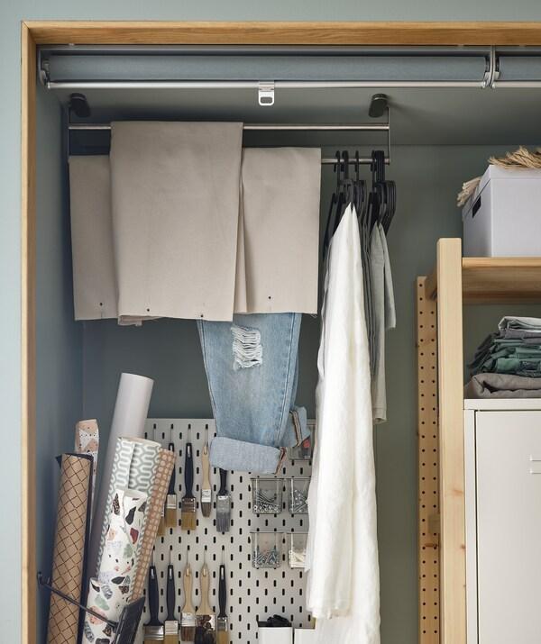 Une alcôve aménagée pour ranger divers accessoires de loisir: des étagères, un panneau perforé et un porte-serviettes fixé au plafond, des rideaux en tissu.