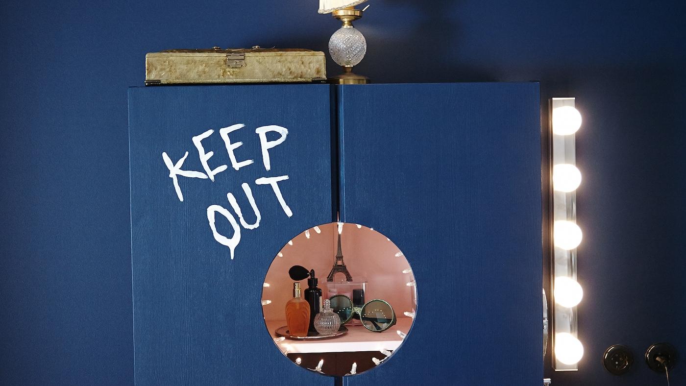 """Une armoire bleue arborant l'inscription """"Keep out"""" peinte. Un cercle y a été découpé afin de révéler des flacons de parfum et des lunettes de soleil."""