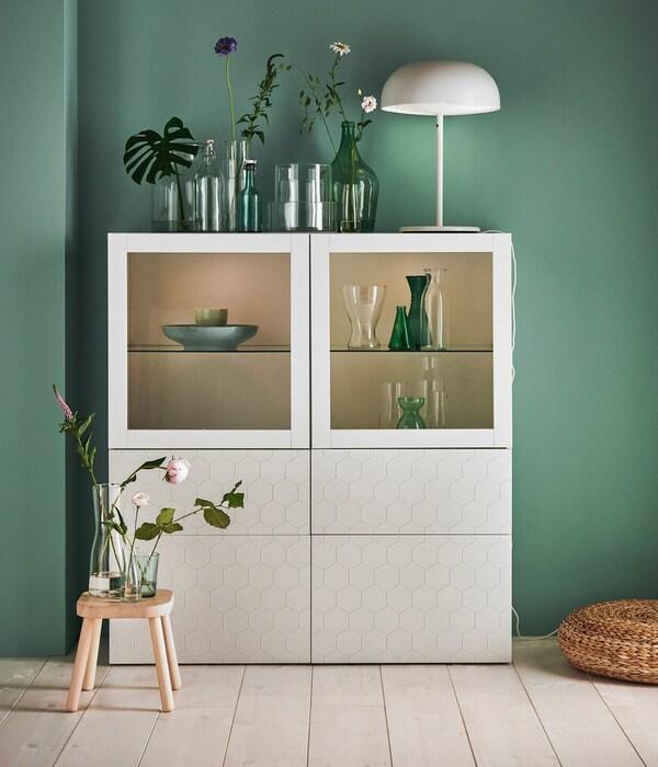 Une armoire de salon avec vitrine éclairée et portes fermées de couleur blanche.
