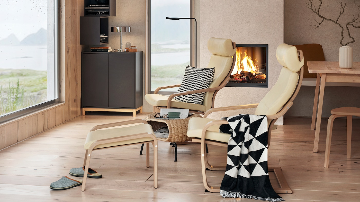 Une armoire EKET en gris foncé avec des portes équipées d'un système de poussoir, dans un séjour avec des fauteuils et deux fenêtres.