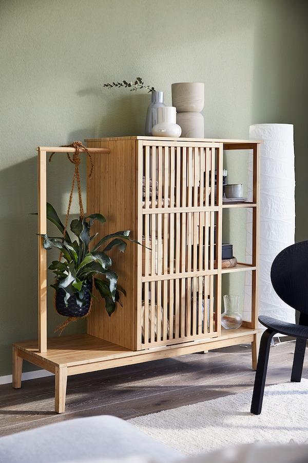 Une armoire en bambou avec des plantes et des vases.