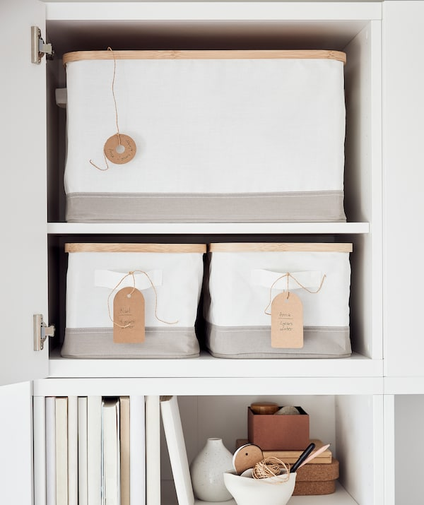 Une armoire, la porte ouverte, dévoilant des boîtes de rangement RABBLA portant des étiquettes écrites à la main. Sous l'armoire, une étagère avec des livres.