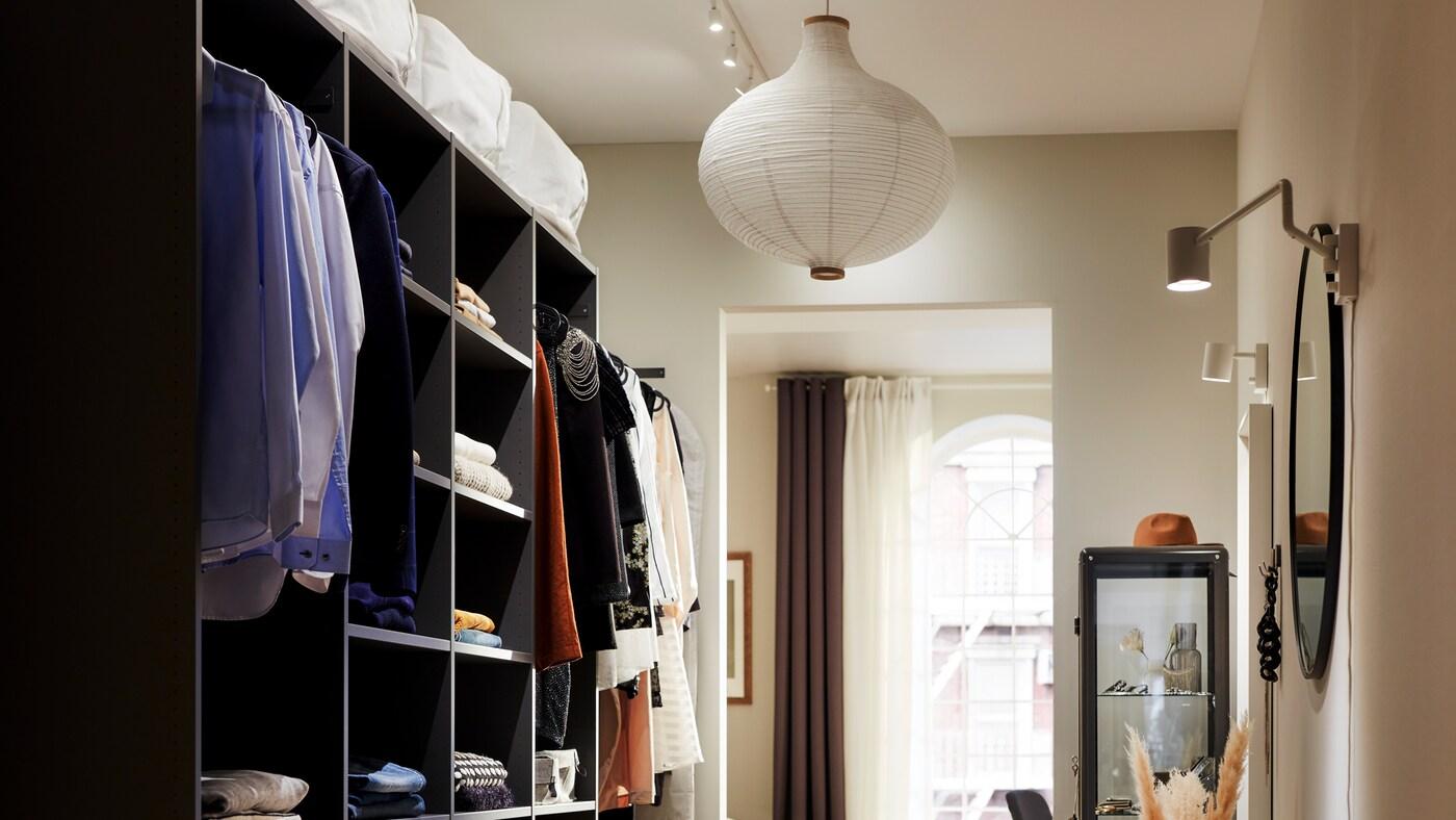 Une armoire-penderie ouverte AURDAL avec des vêtements pliés sur les tablettes et suspendus à des tringles face à un mur avec des miroirs et des lampes.