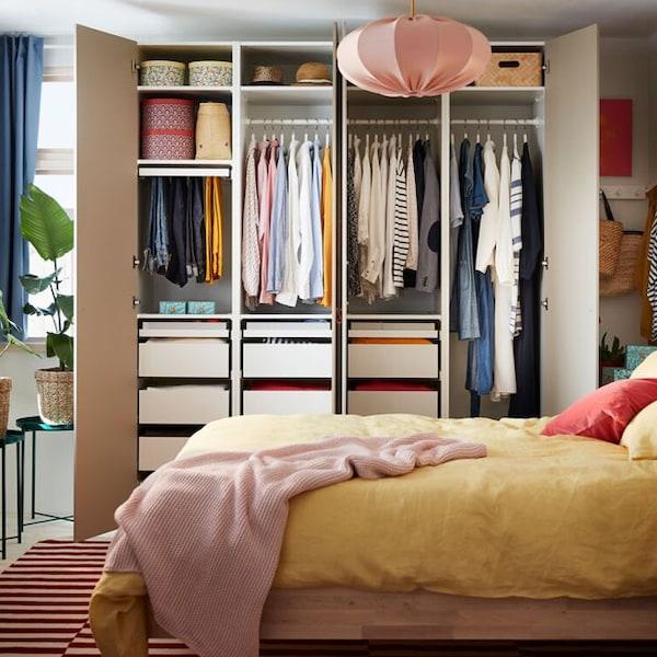 Une armoire-penderie ouverte PAX/REINSVOLL remplie de vêtements, près d'un lit recouvert de literie jaune PUDERVIVA et d'un jeté INGABRITTA.