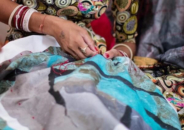 Une artisane indienne applique des broderies sur une housse de coussin ornée d'un imprimé moderne et irrégulier turquoise, gris et noir.