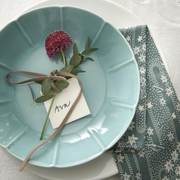 Une assiette bleue sur laquelle est posée une fleur rose.
