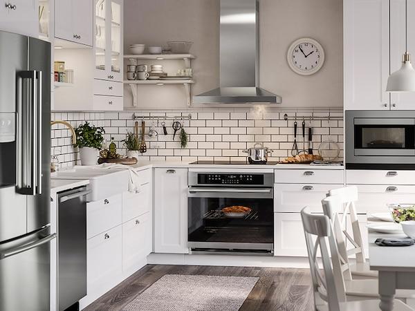 Une belle cuisine moderne avec des armoires blanches et des appareils en acier inoxydable.
