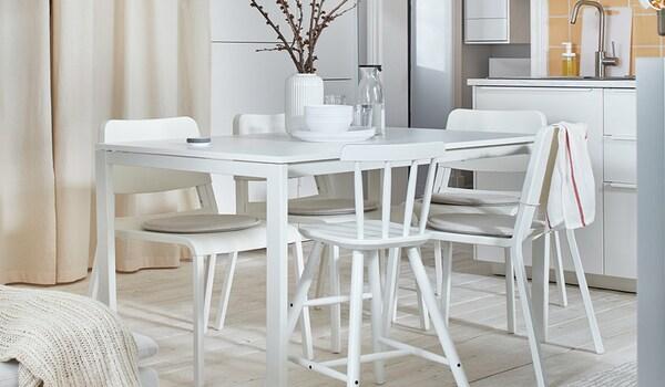 Une belle salle à manger lumineuse avec des meubles blancs.