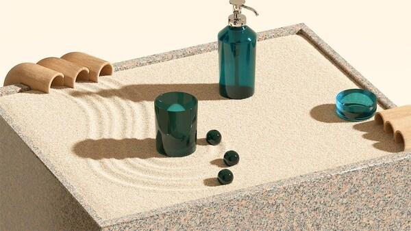 Une boîte de granite remplie de sable sur lequel sont disposés des accessoires verts de salle de bains et trois billes en verre.