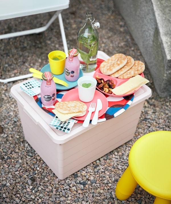 Une boîte rose SOCKERBIT fait office de petite table avec de la vaisselle HEROISK, placée entre une chaise FEJAN et un tabouret MAMMUT.