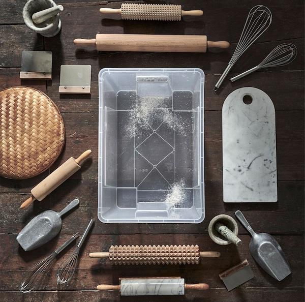 Une boîte transparente SAMLA sur un plancher de bois, entouré de divers accessoires à pâtisseries.