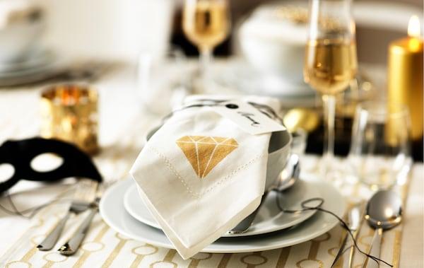 Une bonne idée pour décorer la table consiste à personnaliser des serviettes en tissu. Avec, par exemple, un motif de diamant doré peint au pochoir sur des serviettes blanches GULLMAJ de chez IKEA. Posez-les ensuite sur les assiettes et les bols blancs, sur un set de table blanc et doré.