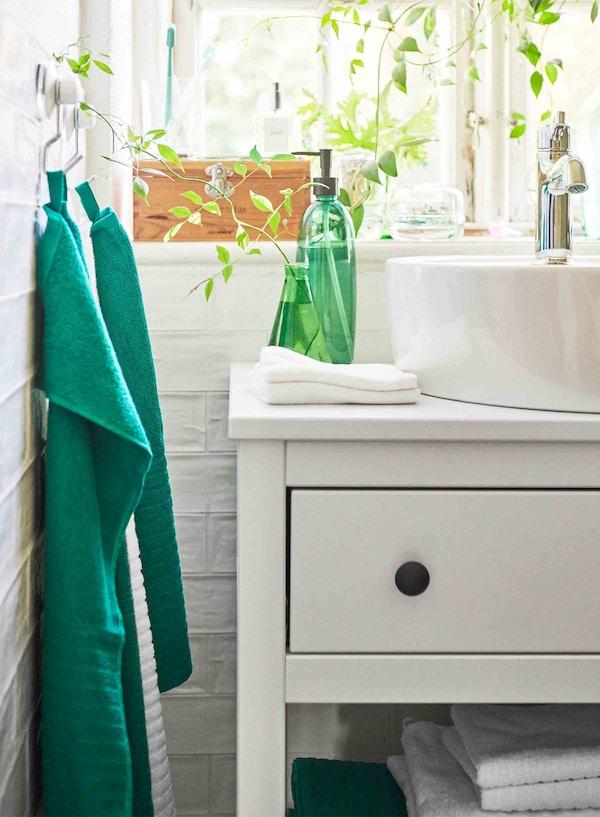 Une bouteille et un vase vert vif sont posés sur un meuble lavabo blanc, et deuxserviettes vertes sont accrochées à gauche.