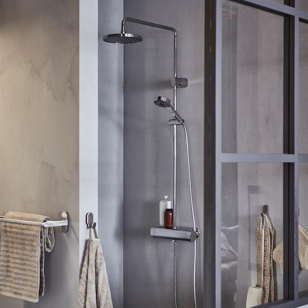 Une cabine de douche grise avec pommeau supérieur et douchette, avec des serviettes beiges sur des crochets.