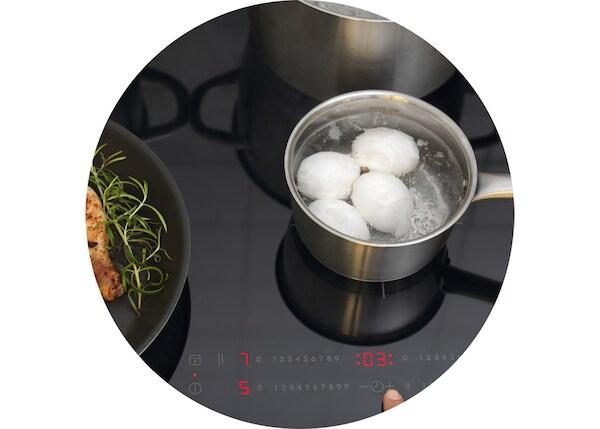 Une casserole IKEA dans laquelle cuisent des œufs durs sur une table de cuisson à induction IKEA.