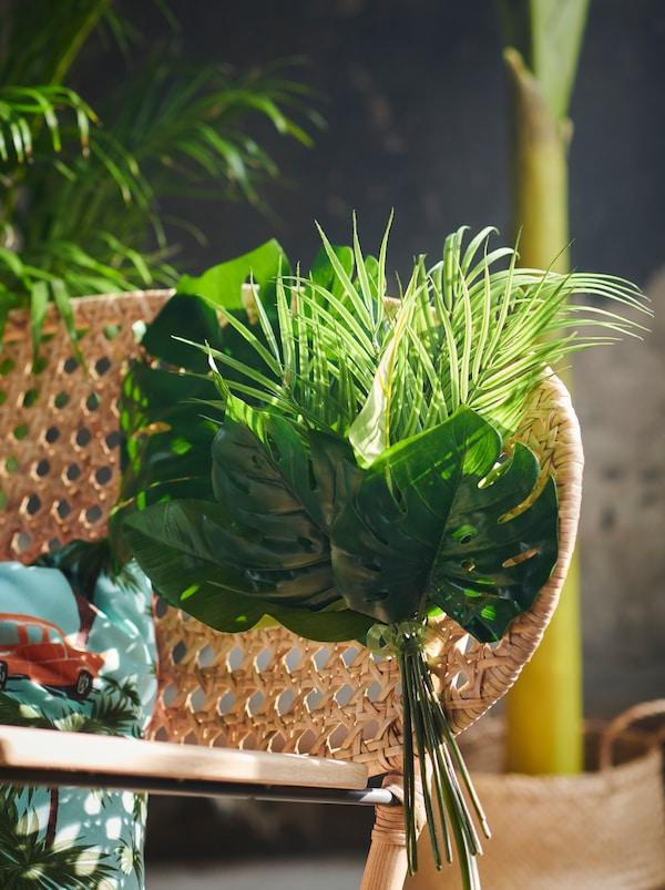 Une chaise à bascule en rotin GRÖNADAL tissée à la main décorée d'un bouquet de feuilles artificielles SMYCKA.