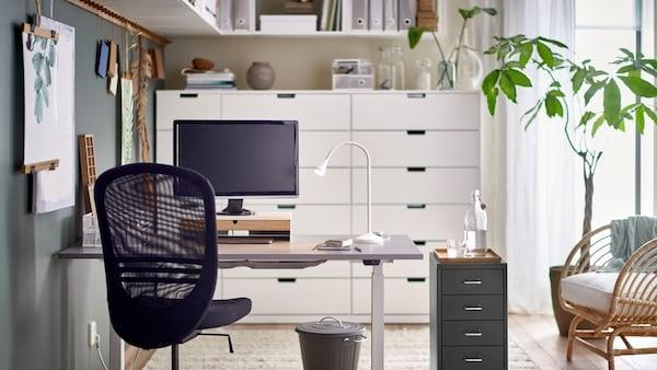 Une chaise de bureau noire FLINTAN et un caisson à tiroirs HELMER près d'un bureau assis-debout avec une lampe de travail et un écran d'ordinateur.