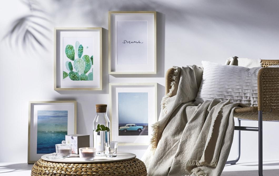 Une chaise en osier et un pouf meublent la pièce, des œuvres d'art habillent le mur blanc.