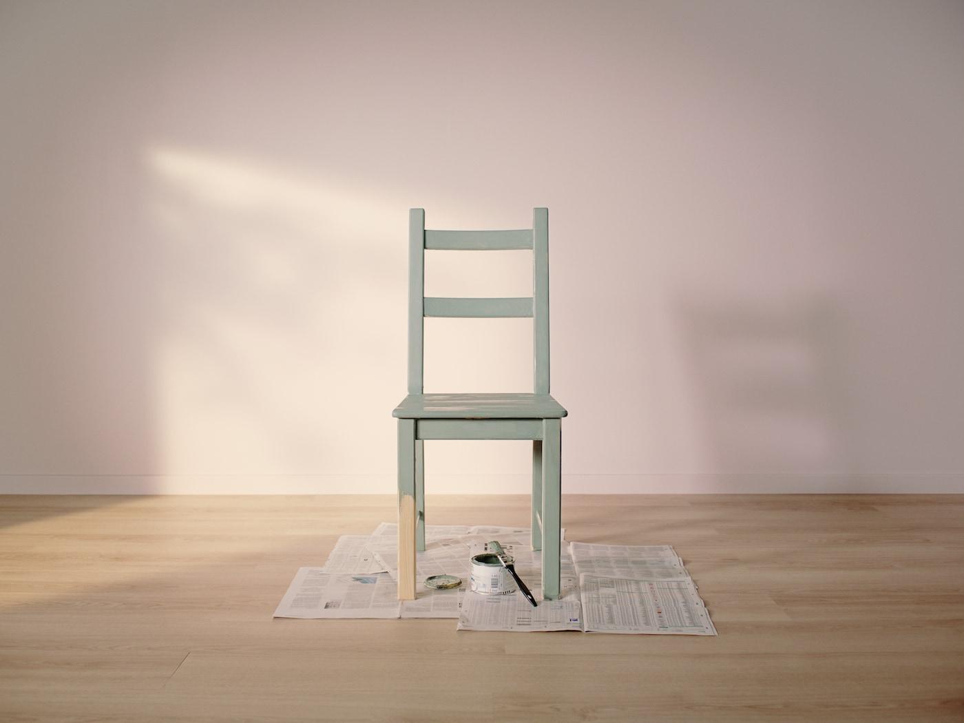 Une chaise IVAR en pin entièrement peinte en vert sauf pour la moitié d'un pied est posée sur du papier journal à côté d'un pot de peinture et d'un pinceau.