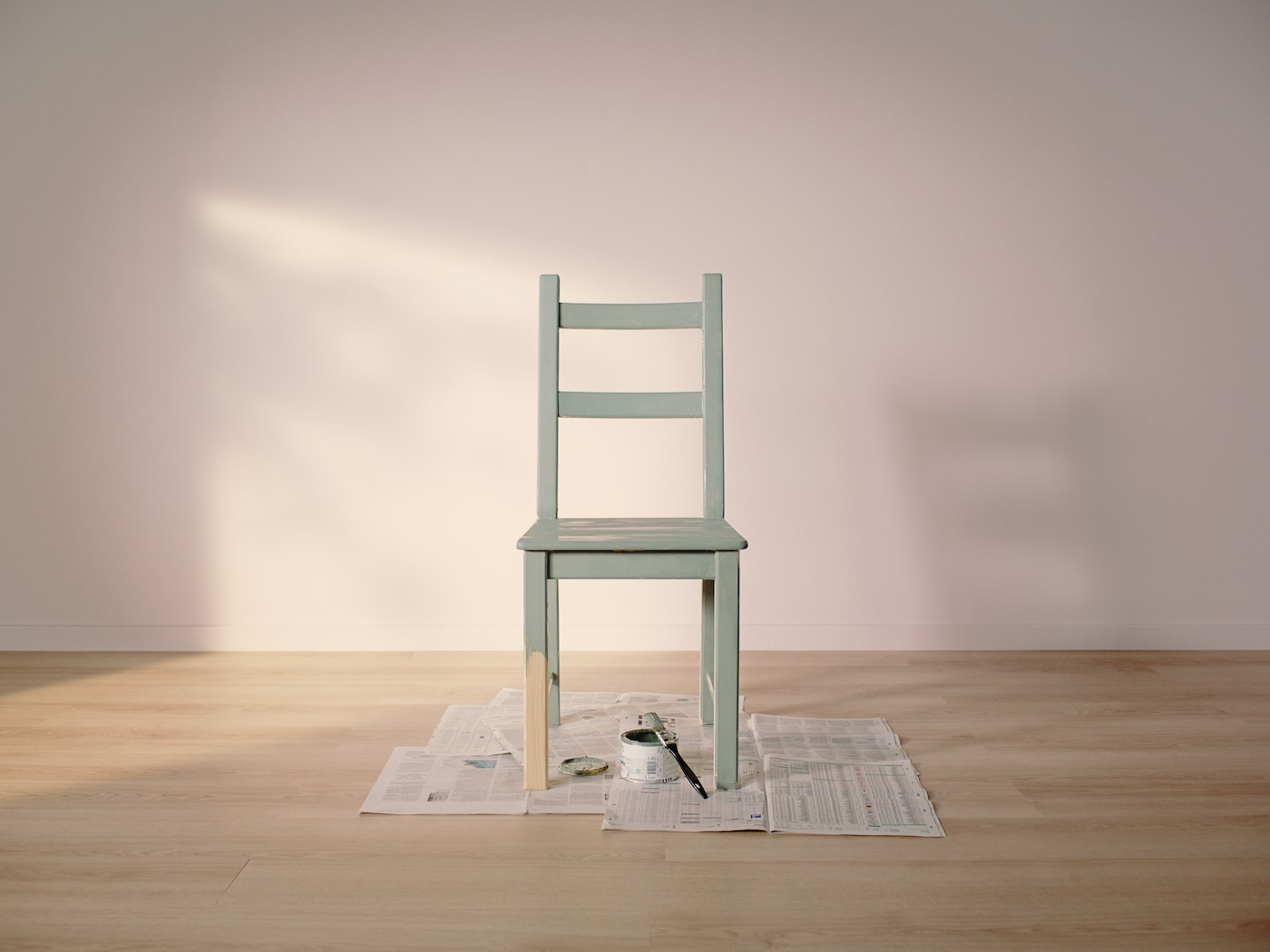 Une chaise IVAR en pin, peinte en vert sauf la moitié d'un pied, posée sur un journal avec un pot de peinture et un pinceau.
