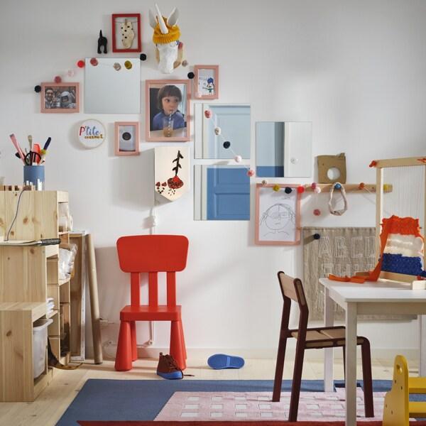 Une chaise MAMMUT rouge à côté d'un rangement TROFAST contre un mur blanc couvert d'images et d'objets dans des cadres FISKBO roses.
