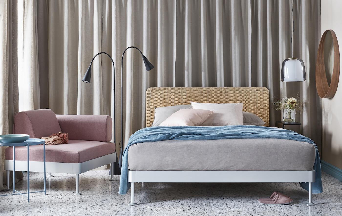 Une chambre à coucher aux tons neutres doux gris, beige et rose avec un lit double, un lampadaire, un fauteuil et une table d'appoint.