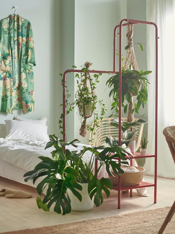 Une chambre à coucher avec de petites et de grandes plantes au bout du lit, suspendues et déposées sur un portant NIKKEBY rouge.