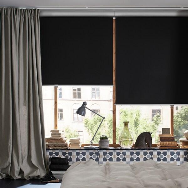 Une chambre à coucher avec un lit au milieu et des fenêtres avec un rideau INGERT et des stores à enrouleur opaques TRETUR à moitié baissés.