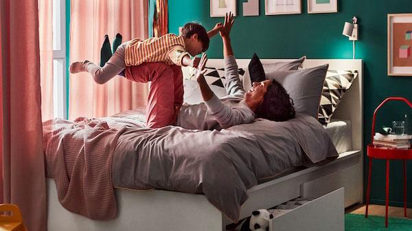 Une chambre à coucher avec un papa couché sur le dos, ses jambes et ses bras en l'air, occupé à jouer à l'avion avec son enfant.