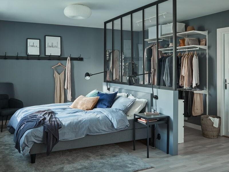 Une chambre à coucher dans différentes nuances de bleu avec un lit matelassé, beaucoup de coussins, un fauteuil à oreilles, des livres et un grand tapis.