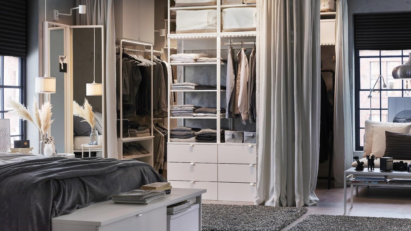 Une chambre à coucher dans les tons blancs et gris, avec garde-robe ouverte, rideaux gris clair et tapis gris foncé.