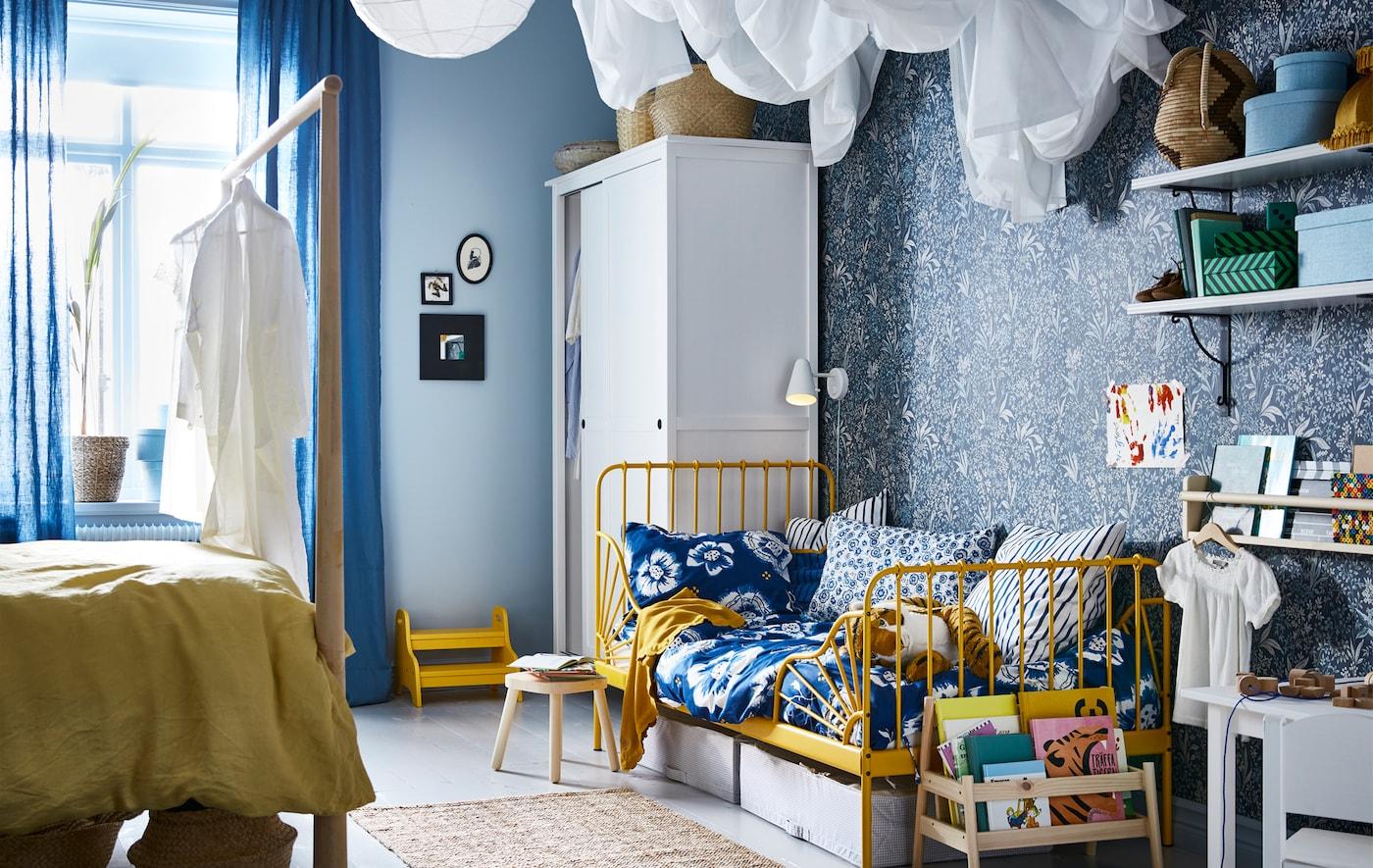 Une chambre à coucher dans une palette bleu et jaune, avec un lit adulte d'un côté et un lit d'enfant de l'autre.