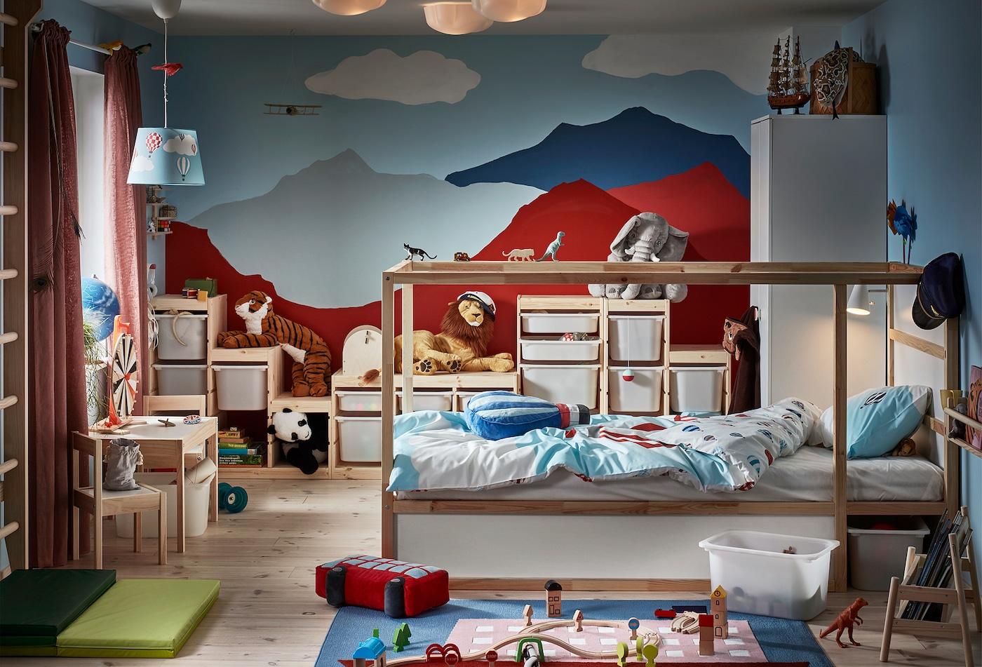 Une chambre à coucher d'enfants avec des montagnes peintes sur le mur à l'arrière-plan. Un lit réversible, des barres murales, des jouets et différents rangements.