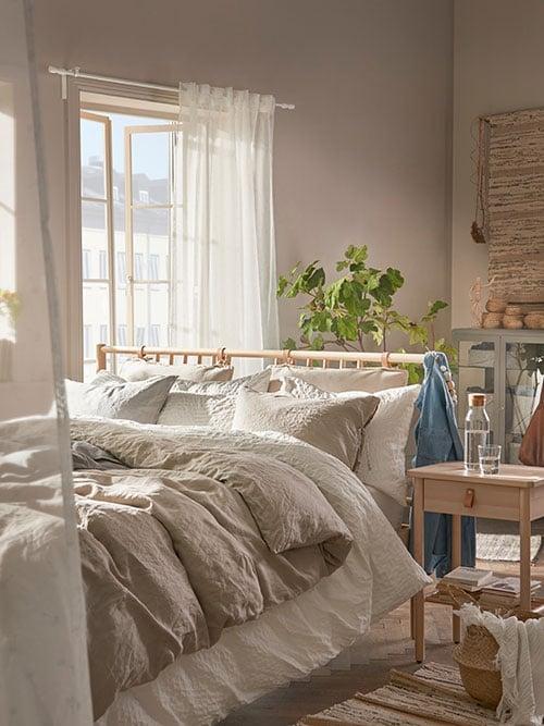 Une chambre à coucher où se trouvent un lit en bouleau avec sommier à lattes, une table de chevet assortie, avec des accents en cuir.
