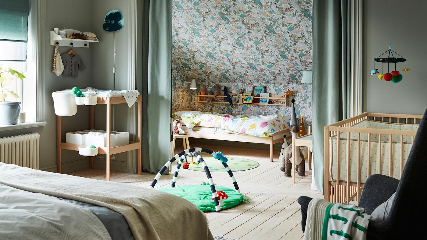 Une chambre à coucher vert clair contenant un lit double ainsi qu'un lit bébé, un lit et une table à langer SNIGLAR, avec un portique pour bébé KLAPPA sur le sol.