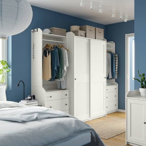 Une chambre aux murs bleus avec une grande armoire-penderie HAUGA blanche équipée de portes coulissantes.