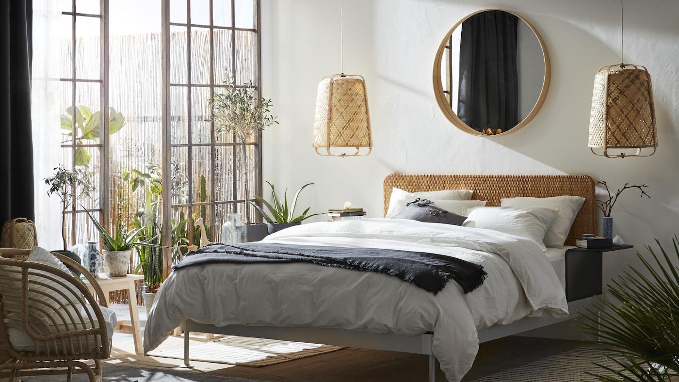 Une chambre avec de grandes portes-fenêtres et un litDELAKTIG. Un miroirSTOCKHOLM est placé sur le mur, au-dessus de deux suspensions.