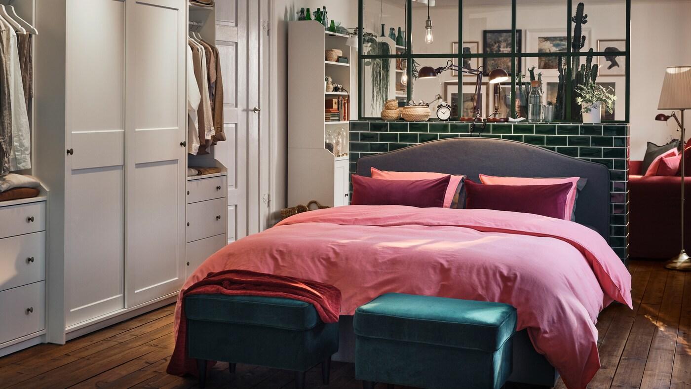 Une chambre avec des armoires-penderies blanches, un lit rembourré gris, du linge de lit brun-rouge clair et deux tabourets verts.